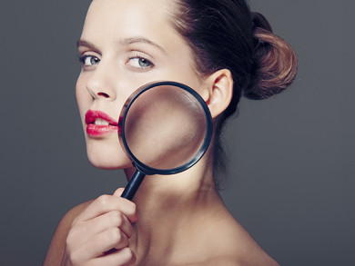 Woman holding magnifying glass to face