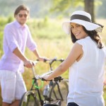 Happy young couple with bicycles smiling toward camera . Holidays and relax