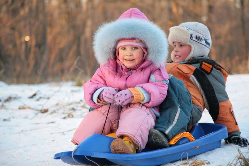 children  sits on plastic sled in park in winter