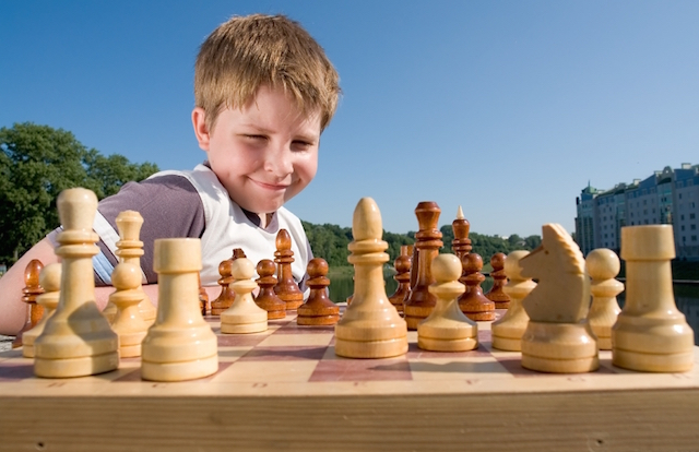 A little boy chess with sky at background