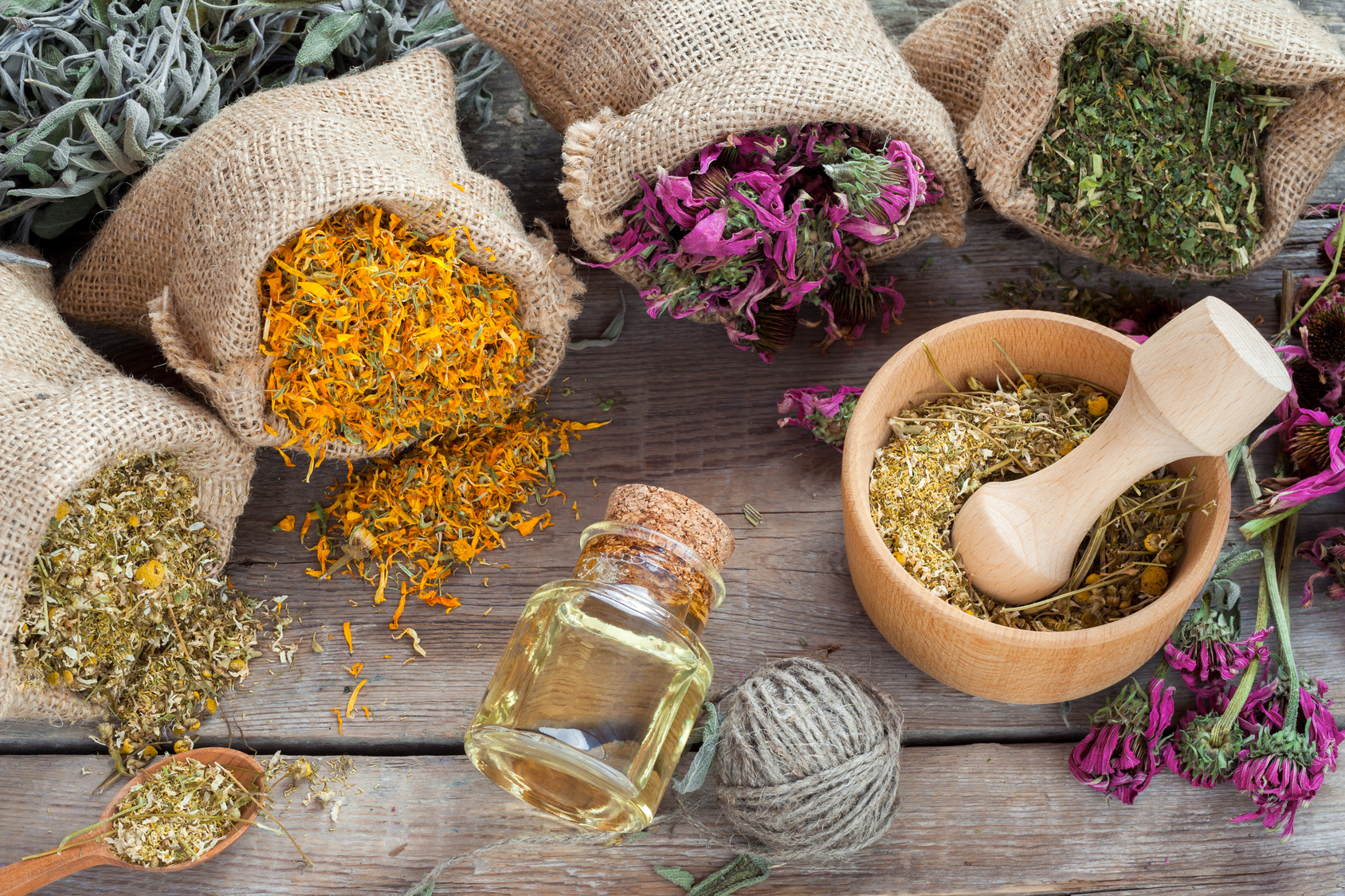 Healing herbs in hessian bags, wooden mortar with chamomile and