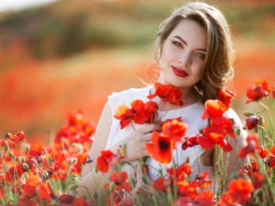 Pretty woman in field of poppy flowers, spring time