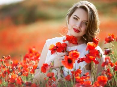 Pretty woman in field of poppy flowers, spring time