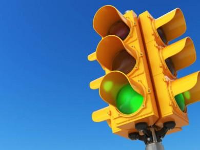 Traffic light with green color on blue sky background. 3d illustration